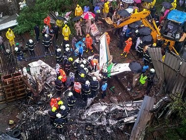 Rescue personnel at the site of the crash in Mumbai's Ghatkopar. PTI