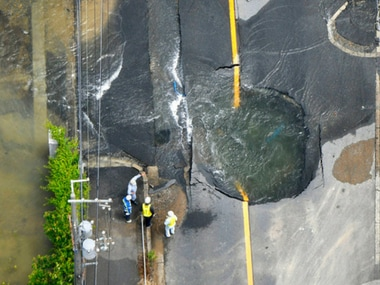 Water floods out from crack in the road, following an earthquake in Takatsuki, Osaka. Kyodo News via AP