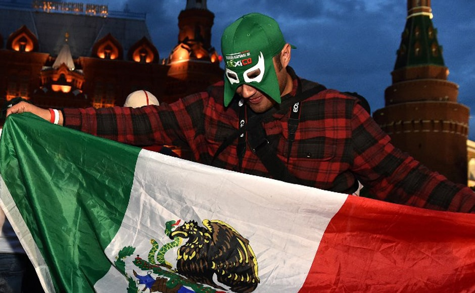 A fan of Mexico's national football team waves a Mexican flag as he cheers outside the Kremlin on 11 June, 2018, in Moscow, ahead of the Russia 2018 football World Cup. AFP.