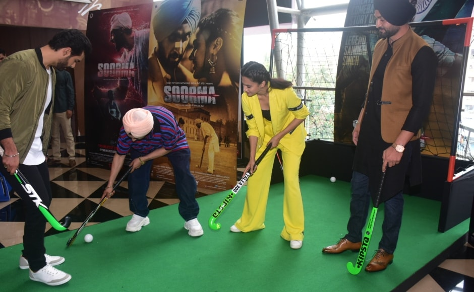 The cast, including Diljit Dosanjh and Taapsee Pannu posing with a hockey bat at the trailer launch.