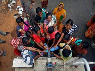 People fill bottles with water from a municipal truck in India. Reuters