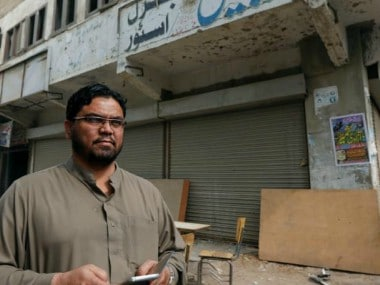 Zakir Hanif, an activist of Awami National Party, points to the ceiling of his pharmacy store which was bombed by the Tehreek-e-Taliban Pakistan. Reuters