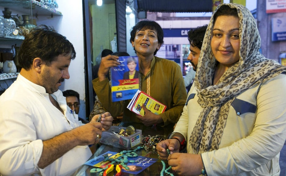 Pakistani transgender election candidate Nadeem Kashish (centre) visits shops during her election campaign, in Islamabad. The Pakistani election commission has for the first time allowed the transgender community to participate in an election. AP
