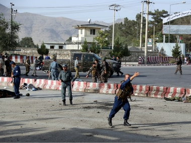 An Afghan police officer runs past the bodies of security personal after an attack near the Kabul Airport, in Kabul, Afghanistan, Sunday. AP