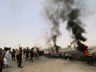 Protesters burn tires and block the road at the entrance to the city of Basra. Reuters