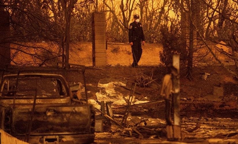 California Highway Patrol officer Gavin Graham surveys homes leveled by the Carr Fire in the Lake Keswick Estates area of Redding. AP