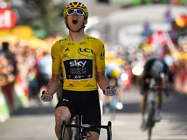 Great Britain's Geraint Thomas, wearing the overall leader's yellow jersey, celebrates as he crosses the finish line to win the twelfth stage of the 105th edition of the Tour de France cycling race, between Bourg-Saint-Maurice - Les Arcs and l'Alpe d'Huez, on July 19, 2018. / AFP PHOTO / Marco BERTORELLO