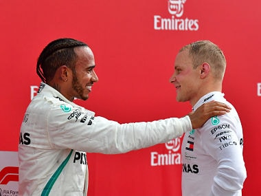 Winner Mercedes' British driver Lewis Hamilton (L) talks with second placed Mercedes' Finnish driver Valtteri Bottas after the German Formula One Grand Prix at the Hockenheim racing circuit on July 22, 2018 in Hockenheim, southern Germany. / AFP PHOTO / Andrej ISAKOVIC