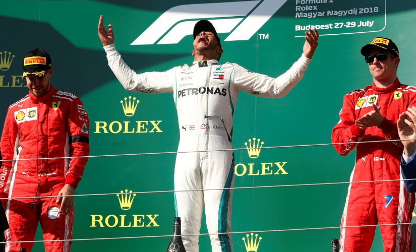 Lewis Hamilton celebrates his victory at Hungary as Ferrari takes the next two spots. Reuters