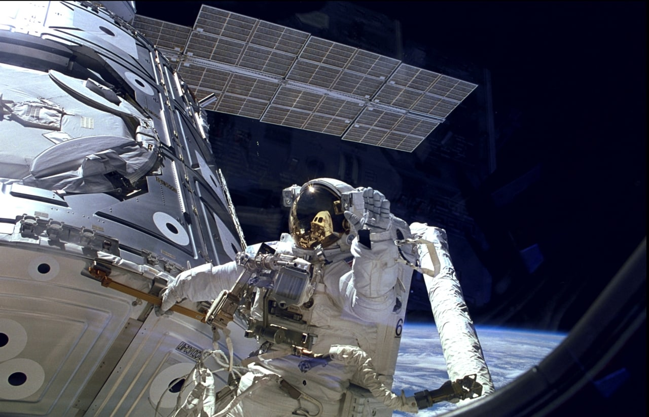 Astronaut James Newman waves during a spacewalk outside the International Space Station. Image courtesy: NASA