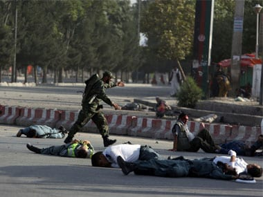 Afghan security personnel and traffic police lie on the ground after a suicide attack near the Kabul Airport. AP
