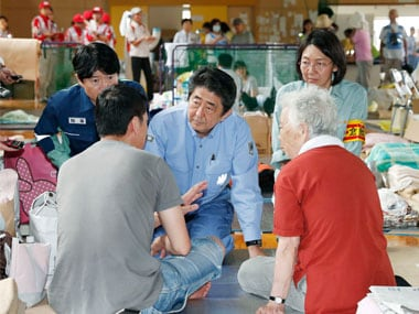 Japanese Prime Minister Shinzo Abe, center, listens to an evacuee during a visit to an evacuation center in Kurashiki, Okayama prefecture. AP
