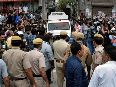 An ambulance in Delhi carries away the bodies of 11 members of a family who were found hanging from an iron grill in a house, in Burari area. PTI