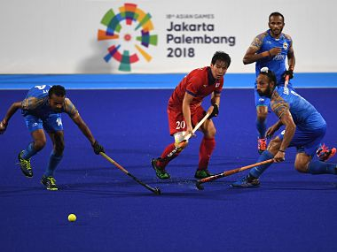 India's Lalit Kumar Upadhyay (L) and Japan's Masaki Ohashi (C) compete for the ball during the men's hockey pool B match between India and Japan at the 2018 Asian Games in Jakarta on August 24, 2018. / AFP PHOTO / SONNY TUMBELAKA
