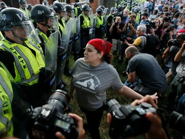 A protester confronts riot gear-clad police on the campus of the University of Virginia during a rally to mark the anniversary of last year's Unite the Right rally in Charlottesville on Saturday. AP