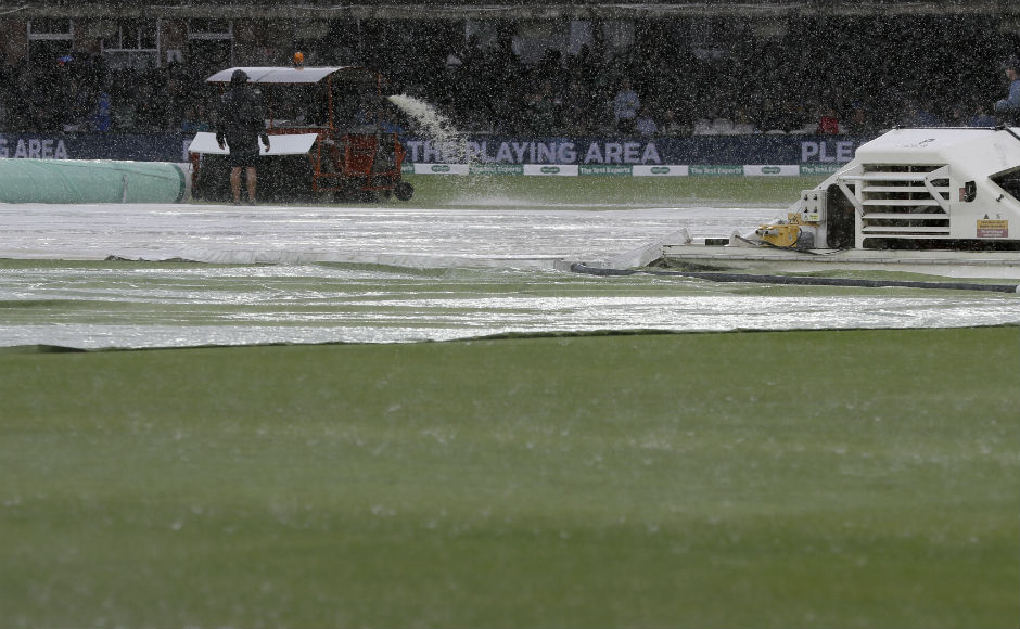 The ground staff bring the covers out during a spell of rain on Day 2. AP