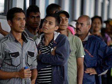 Venezuelan migrants wait at an immigration office to get a humanitarian document to continue their travel in Tumbes, Peru. AP