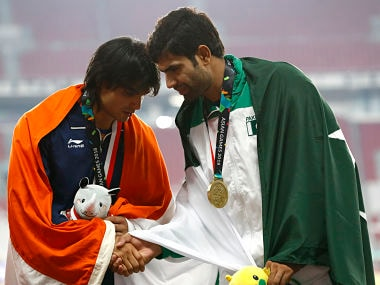 Men's javelin bronze medalist Pakistan's Arshad Nadeem, right, congratulates gold medalist India's Neeraj Chopra on the podium during the athletics competition at the 18th Asian Games in Jakarta, Indonesia, Monday, Aug. 27, 2018. (AP Photo/Bernat Armangue)