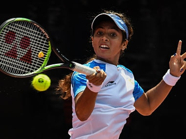 India's Ankita Ravinderkrishan Raina hits a return against Indonesia's Beatrice Gumulya in their women's singles tennis match during the 2018 Asian Games in Palembang on August 20, 2018. / AFP PHOTO / Mohd RASFAN