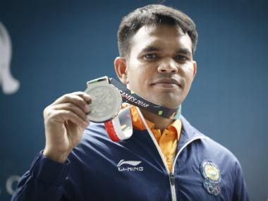 Deepak Kumar displays the silver medal he won in the Men's 10m Air Rifle event. AP