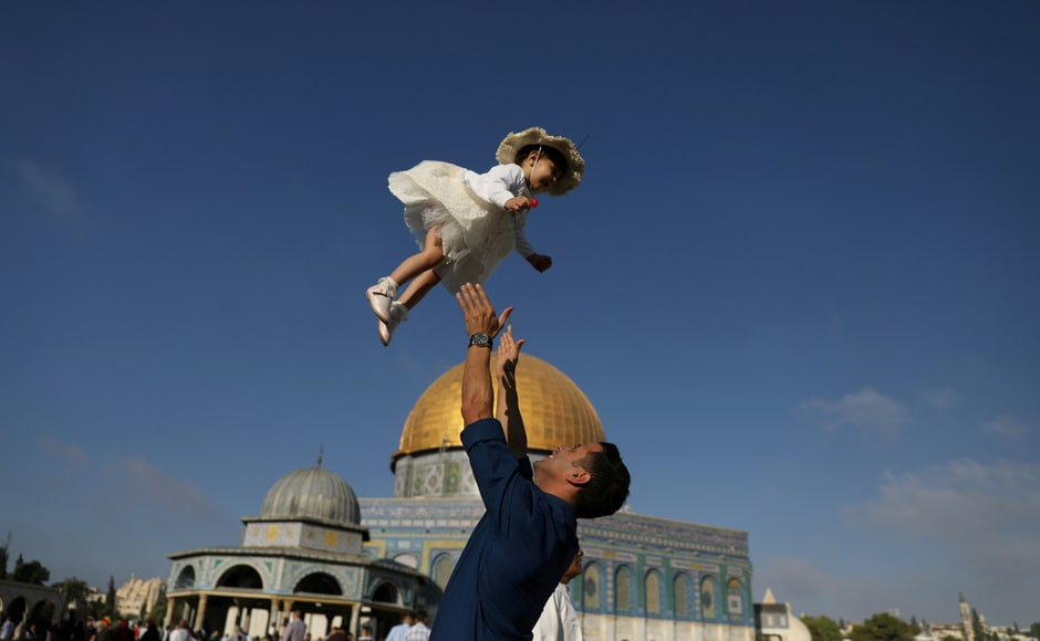 A man in Palestine plays with his child following morning prayers that mark the first day of Eid al-Adha celebrations, on the compound known to Muslims as al-Haram al-Sharif and to Jews as Temple Mount in Jerusalem's Old City on 21 August, 2018. Reuters/Ammar Awad