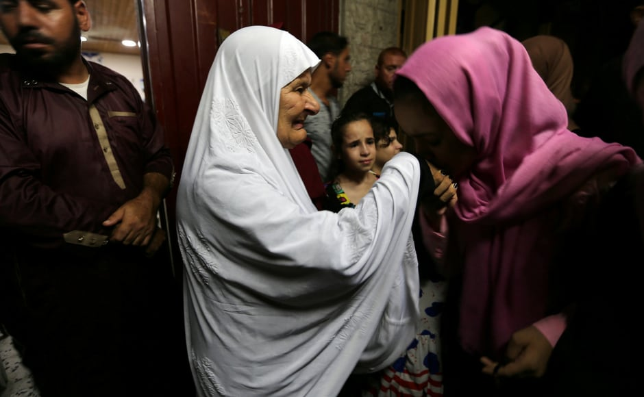 A Palestinian girl kisses the hand of her grandmother who leaves Gaza for the annual Haj pilgrimage in Mecca, in the southern Gaza Strip on 3 August, 2018. Nearly 2 million Muslims, including 1.68 million from abroad, flood Mecca's narrow streets for the annual rite which started on Sunday, 19 August, 2018. Reuters/ Ibraheem Abu Mustafa