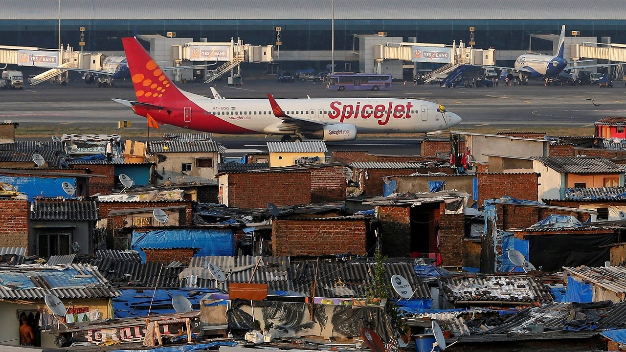 A SpiceJet passenger aircraft taxis on the runway at the airport next to a slum area in Mumbai December 19, 2014. Reuters