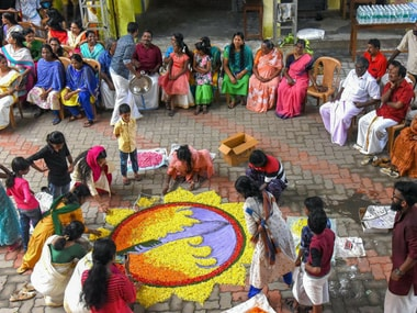 Women make a 'rangoli' as they celebrate 'Onam' at a flood relief camp in Kochi on Saturday. PTI
