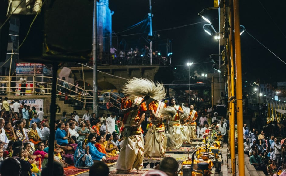 The evening ceremony at the ghats reaches its fever pitch with the final aarti. People swaying. Their faces lit golden in the light of the flames. The fire rising to the sky, reflecting into the cold, dark water below.