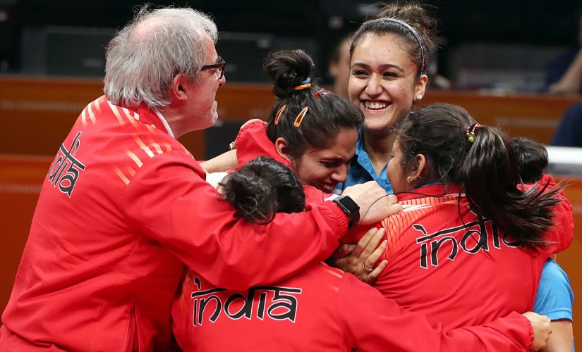 India's women's team celebrate along with coach Massimo Costantini (L), after winning gold at the CWG. Reuters