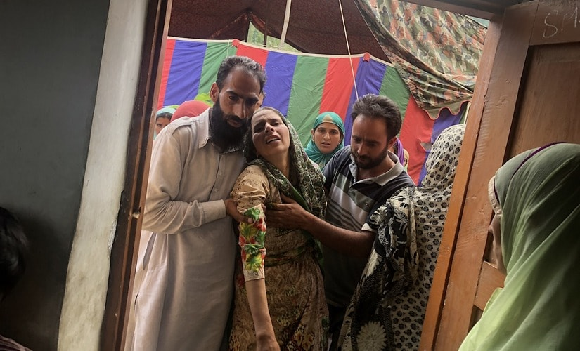 Shareefa, the wife of Tariq Ahmad Malik, entering her house for the first time since her husband was killed. Image: Sameer Yasir