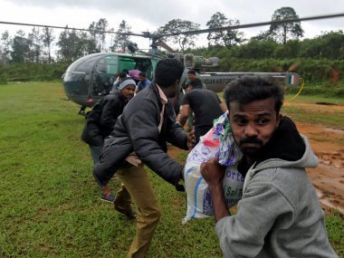 Flood victims unload food and relief material from an Indian Air force helicopter at Nelliyampathy Village in Kerala. Reuters