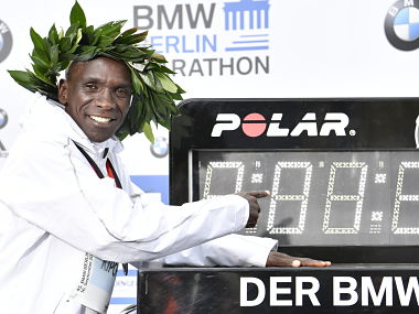 Winner Kenya's Eliud Kipchoge poses with a clock displaying his time after winning the Berlin Marathon. AFP