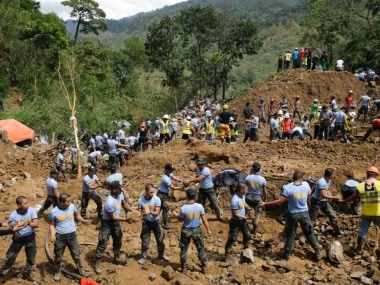 Rescuers move stones at the site where victims are believed to have been buried by a landslide after Typhoon Mangkhut barreled across Itogon, Benguet province, northern Philippines. AP