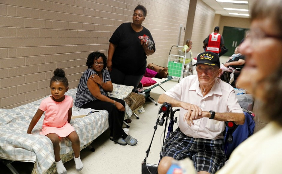Korea war veteran, Ed Coddington, 83, second from right, and wife Esther, 78, wait with Markia McCleod, rear, her aunt Ernestine McCleod and daughter Keymoni, 4, in a shelter for Hurricane Florence to pass after evacuating from their nearby homes. AP