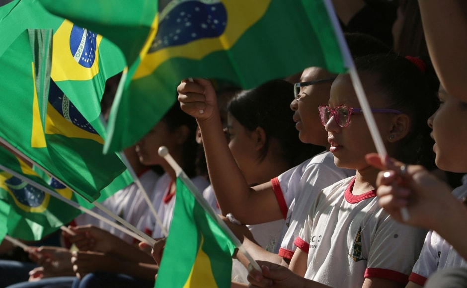 Brazilian children sang the national anthem and waved their country's flag at the parade. AP