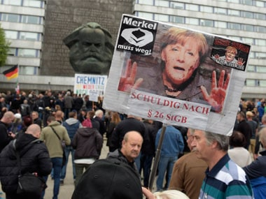"A protestor holds a poster with a photo of Angela Merkel reading 'Merkel must go"" and referring she is guilty of incitement in Chemnitz. AP"