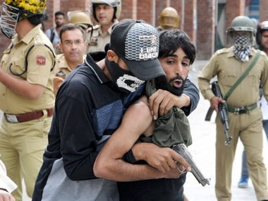 A policeman dressed in civilian clothes arrests a stone pelter. PTI