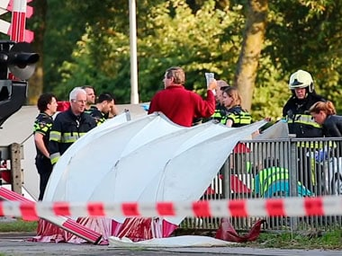 Emergency services attend the scene after a train collided with a cargo bike, at a railway crossing point in the town of Oss. AP