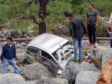 Locals inspect a damaged car washed ashore due to incessant rains at Palampur, Himachal Pradesh. PTI