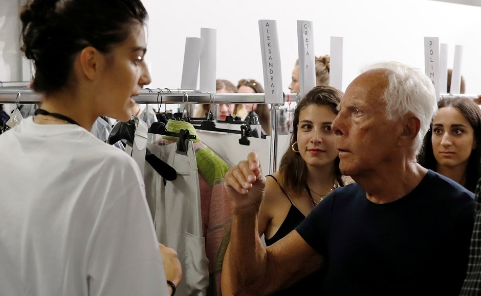 Italian designer Giorgio Armani talks with a model at the backstage before the Emporio Armani show at the Linate Airport during Milan Fashion Week Spring 2019 on 20 September. Reuters/Stefano Rellandini