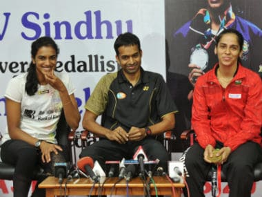 Indian badminton players Pusarla Venkata Sindhu (L) and Saina Nehwal (R) look on as their coach Gopichand (C) speaks during a press conference in Hyderabad. AFP