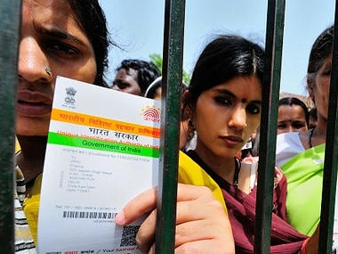 Women hold up their Aadhaar cards. Getty