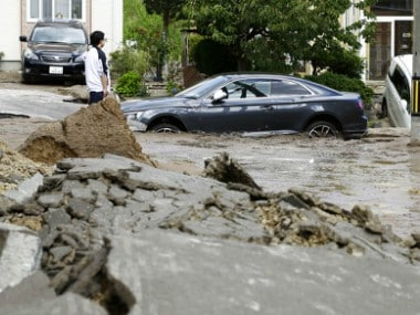 Cars are stuck in mud-covered road after an earthquake in Sapporo, Hokkaido, northern Japan. AP
