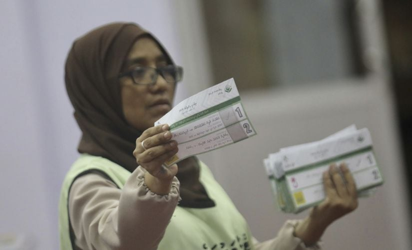 A Maldivian polling worker shows a ballot paper to monitors as she counts votes, following the end of the presidential election day in Male. AP