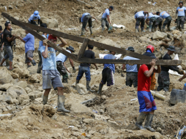 Miners carry remains of structures at the site where victims are believed to be buried in a landslide set off by Typhoon Mangkhut as it lashed across Itogon, Benguet province, Philippines. AP