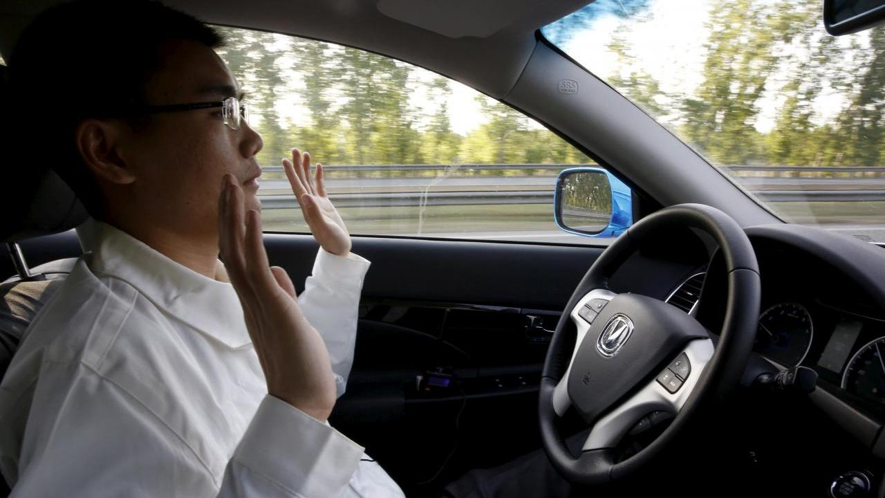 Li Zengwen, a development engineer at Changan Automobile, lifts his hands off the steering wheel as the car is on self-driving mode during a test drive on a highway in Beijing, China, April 16, 2016. REUTERS/Kim Kyung-Hoon/File Photo