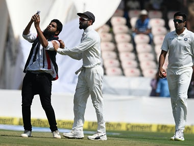 A cricket fan (L) enters the pitch to take a selfie and hug Indian cricket captain Virat Kohli (C) during the first day's play of the second Test cricket match between India and West Indies at the Rajiv Gandhi International Cricket Stadium in Hyderabad on October 12, 2018. (Photo by NOAH SEELAM / AFP) / ----IMAGE RESTRICTED TO EDITORIAL USE - STRICTLY NO COMMERCIAL USE----- / GETTYOUT