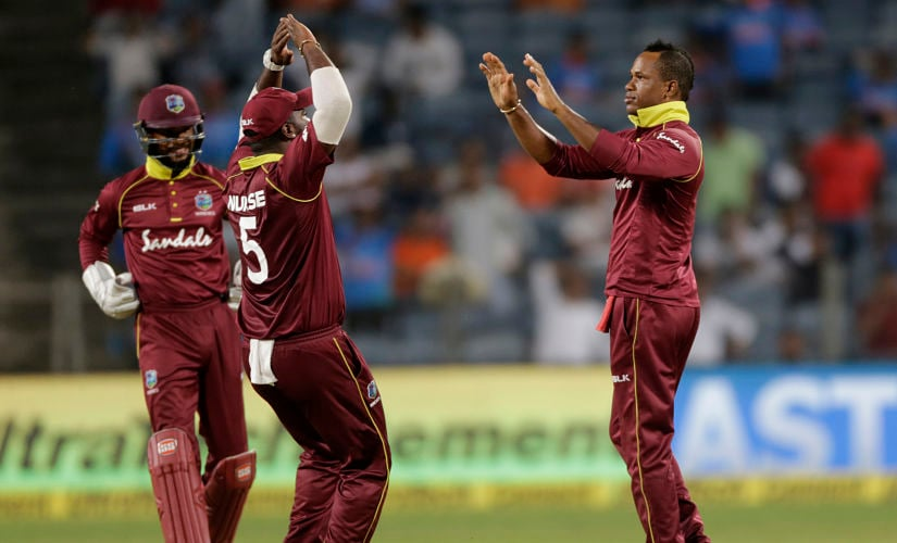 West Indies' Marlon Samuels, right, celebrates the dismissal of India's captain Virat Kohli during the third one-day international cricket match between India and in Pune, India, Saturday, Oct. 27, 2018. (AP Photo/Rajanish Kakade)