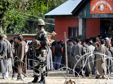 Security personnel stand guard as voters wait in queues to cast their votes at a polling station during the 2nd phase of Municipal elections, in Sumbal area of Bandipora district, Wednesday, 10 October, 2018. PTI